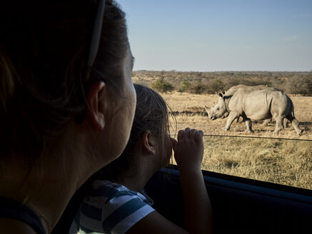 Mother and daughter admiring rhinoceroses through the car window,  Mpumalanga, South Africa - VEGF00242