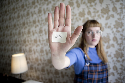 Student showing her hand, a note with the word suffer on her hand - FLLF00181
