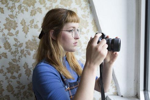 Deutschland,NRW,Ruhrgebiet,Stadt Essen,Studentin schaut durch den Sucher einer Fotokamera - FLLF00190