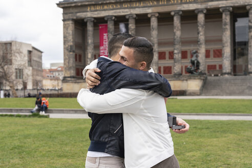 Young man proposing to his  boyfriend, hugging each other, at Lustgarten, Berlin, Germany - TAMF01501