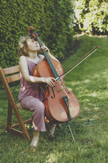 A girl playing the cello  with eyes closed in garden - IHF00024