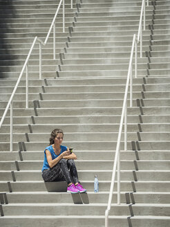 Caucasian woman sitting on staircase texting on cell phone - BLEF03672