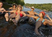 Friends floating on river in inner tubes - BLEF03825