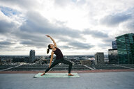 Caucasian woman stretching on urban rooftop - BLEF03834