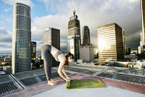 Caucasian woman rolling exercise mat on urban rooftop after yoga - BLEF03852