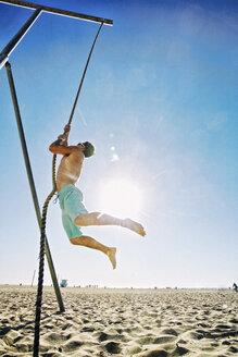 Caucasian man climbing rope on beach - BLEF03858