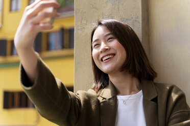 Italy, Florence, happy young woman taking a selfie in the city - FMOF00616
