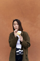 Young woman eating an ice cream cone at an orange wall - FMOF00631