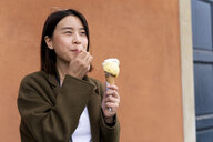 Young woman eating an ice cream cone at an orange wall - FMOF00634
