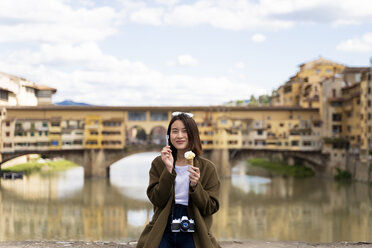 Italy, Florence, young tourist woman eating an ice cream cone at at Ponte Vecchio - FMOF00637