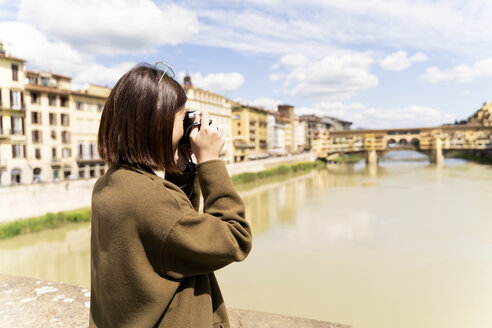 Italy, Florence, young tourist woman taking pictures at Ponte Vecchio - FMOF00640