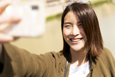 Happy young woman taking a selfie - FMOF00643