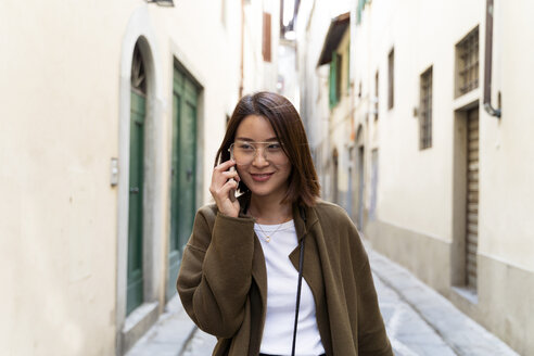 Italy, Florence, young woman on cell phone in an alley - FMOF00646