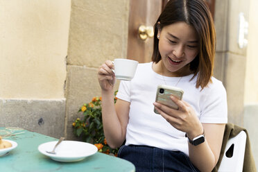 Italy, Florence, young woman using cell phone at an outdoor cafe - FMOF00652