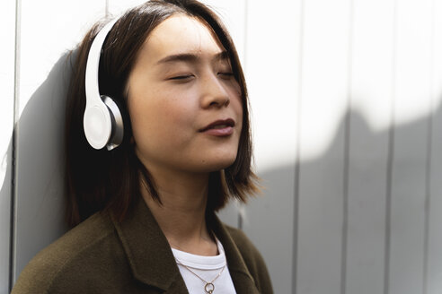 Relaxed young woman with closed eyes listening to music with headphones - FMOF00658