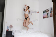 Young woman jumping for joy on her bed - IGGF01167