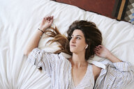Young woman lying on bed, listening music with earbuds - IGGF01170