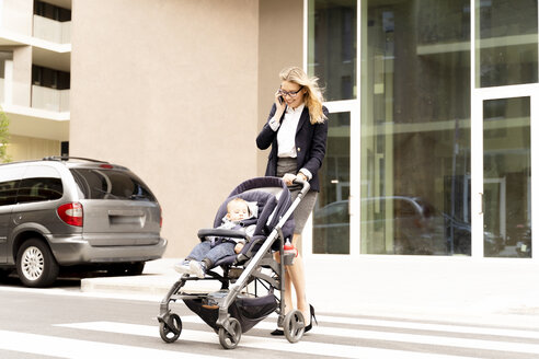 Smiling young businesswoman on the phone crossing street with baby boy in stroller - FMOF00668