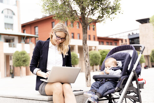 Young businesswoman with baby boy in stroller working on laptop outdoors - FMOF00671