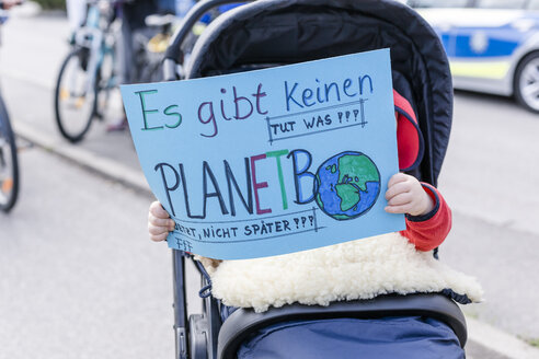 Baby in a pram holding a placard on a demonstration for environmentalism - STBF00350