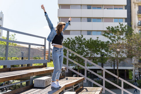 Young woman with raised arms standing on grandstand in Barcelona - AFVF02947