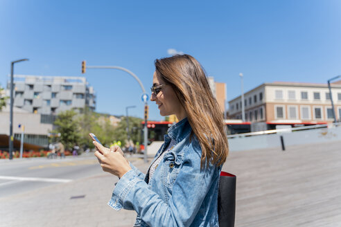 Young woman using smartphone on pedestrian bridge in Barcelona - AFVF02956