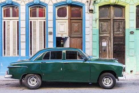 Green vintage car parked in front of house entrances, Havana, Cuba - HSIF00601