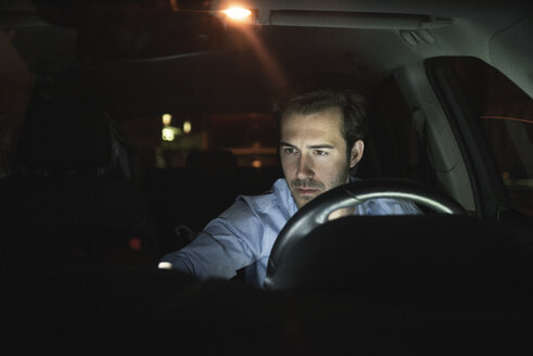 Young man in car at night - UUF17601