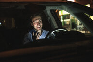 Happy young man using cell phone in car at night - UUF17607