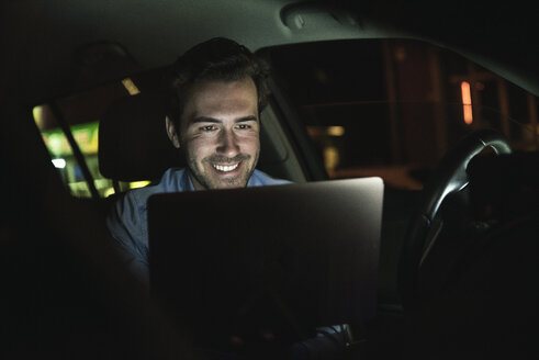 Smiling young man using laptop in car at night - UUF17610