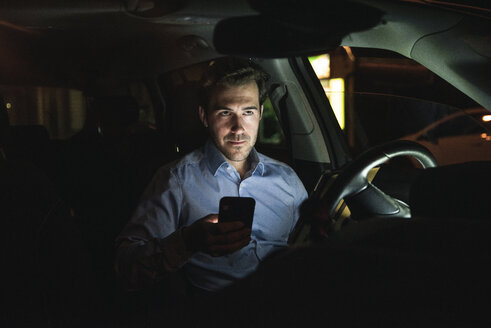 Young man using cell phone in car at night - UUF17613