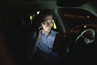 Smiling young man using cell phone and tablet in car at night - UUF17616