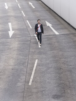 Confident businessman walking on road with arrow signs - UUF17622