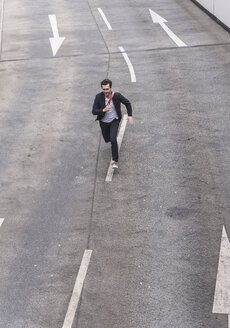 Businessman running on road with arrow signs - UUF17625