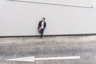 Businessman standing at road with arrow sign - UUF17631