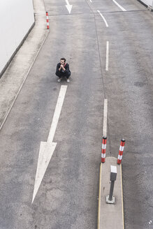Businessman crouching on road with arrow sign - UUF17637