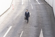 Businessman walking on road with arrow signs - UUF17643