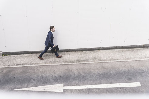 Businessman walking at road with arrow sign - UUF17646