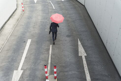Rear view of businessman with umbrella walking on road with arrow signs - UUF17649