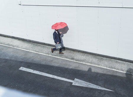 Businessman with umbrella walking at road with arrow sign - UUF17655