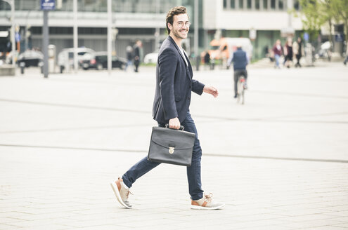 Smiling businessman walking in the city - UUF17658