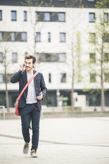 Businessman walking in the city with cell phone and earphones - UUF17661