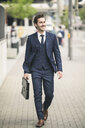 Confident businessman walking in the city - UUF17670