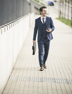 Happy businessman walking in the city with cell phone and earphones - UUF17673
