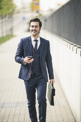Businessman walking in the city with cell phone and earphones - UUF17676