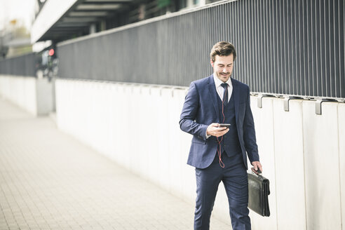 Businessman walking in the city with cell phone and earphones - UUF17679