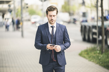 Businessman walking in the city using cell phone - UUF17682
