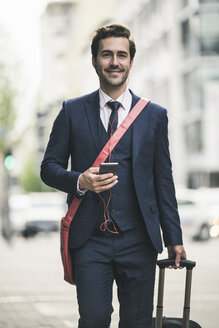 Confident businessman walking in the city with cell phone and suitcase - UUF17685
