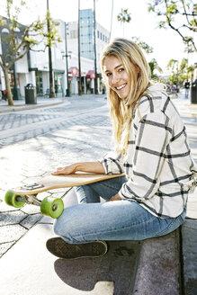 Caucasian woman sitting with skateboard - BLEF03918