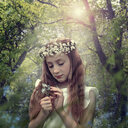 Caucasian girl wearing flower crown in forest - BLEF03954